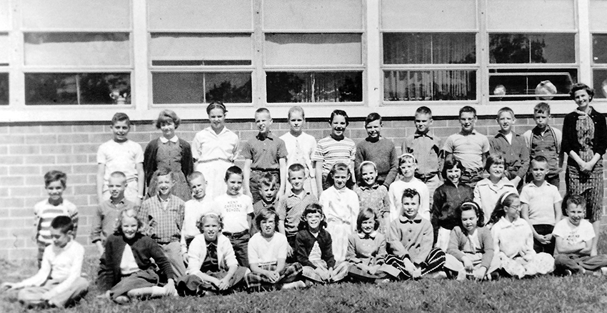 Undated black and white photograph of an unidentified class at Kent Gardens posing with their teacher in front of the building.