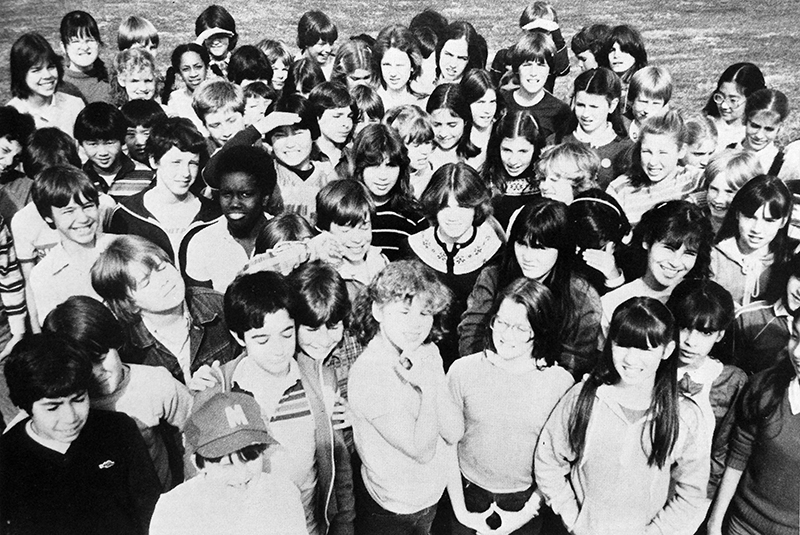 Black and white yearbook photograph of a large group of more than 60 students gathered together outside the school.