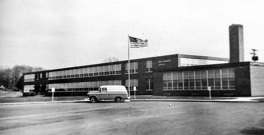 Black and white photograph of the main entrance of Kent Gardens Elementary School taken in 1958. A car is parked in the driveway loop in front of the building.
