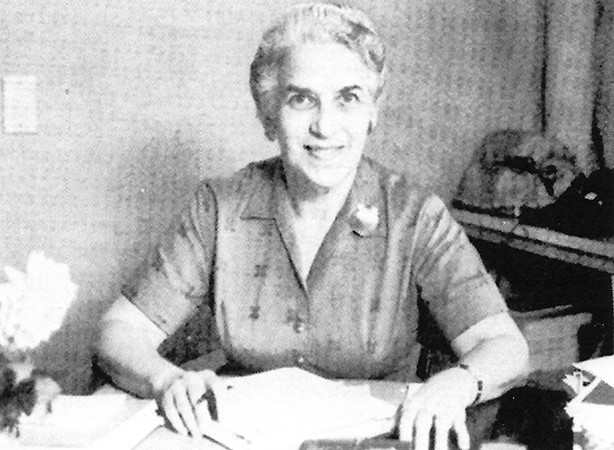 Black and white photograph of Principal Agnes Lawless sitting at her desk.