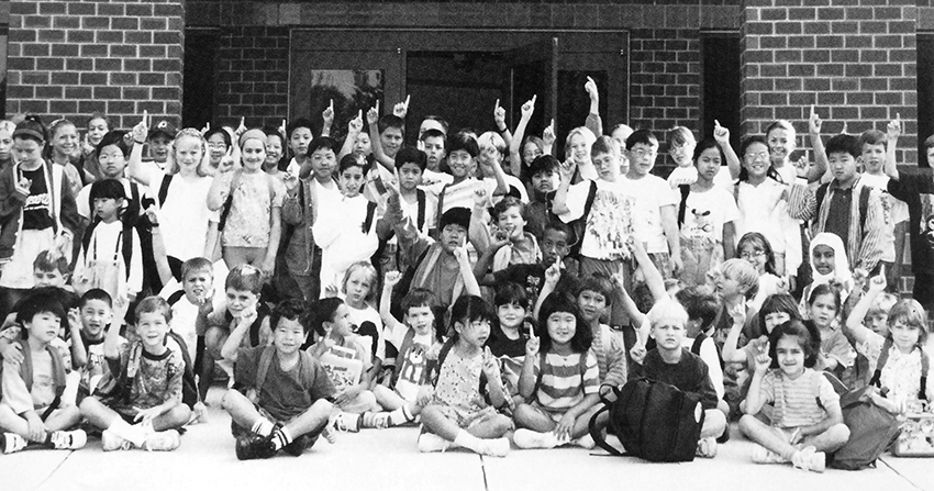Black and white yearbook photograph of a large group of more than 70 students gathered together outside the school. They are posed in front of the main entrance to the building.